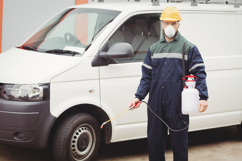 A pest technician with an unmarked van in the background